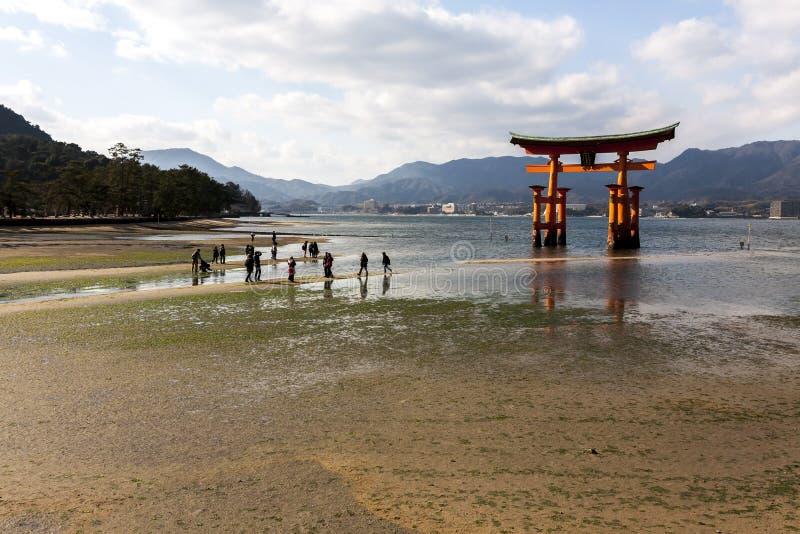 Miyajima, Japan - December 28, 2009: Toeristen die dichtbij Drijvende Tori Gate van Itsukushima-Heiligdom van de kust van Miyajim stock afbeeldingen