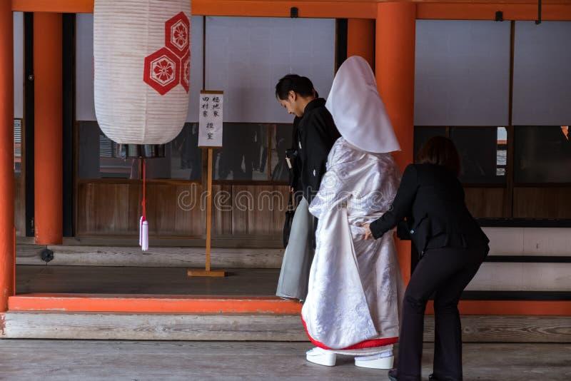 MIYAJIMA JAPAN - FEBRUARI 03, 2018: Japanskt få för brud att gifta sig i den Itsukushima relikskrin som bär vit och röd tradition fotografering för bildbyråer