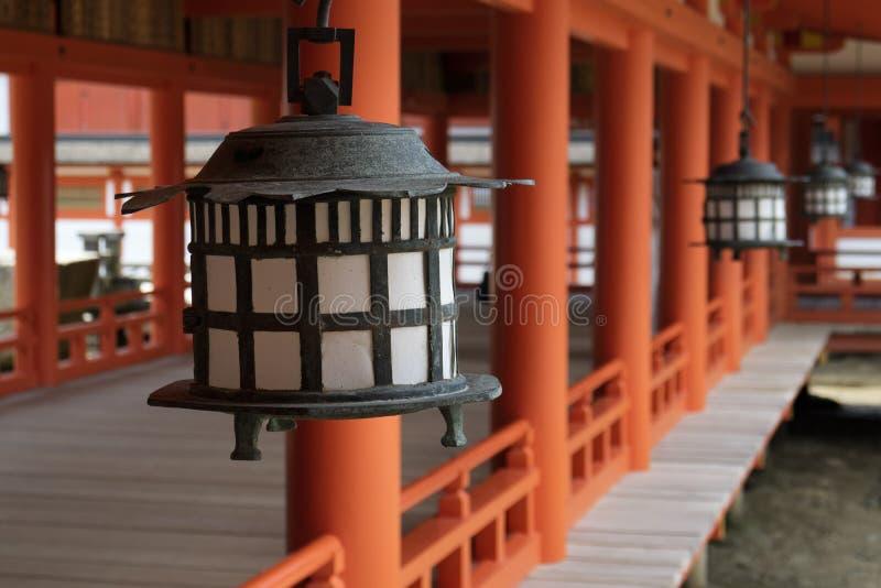 Miyajima - Japan, Maj 26, 2017: Svarta lyktor och röda pelare royaltyfri fotografi
