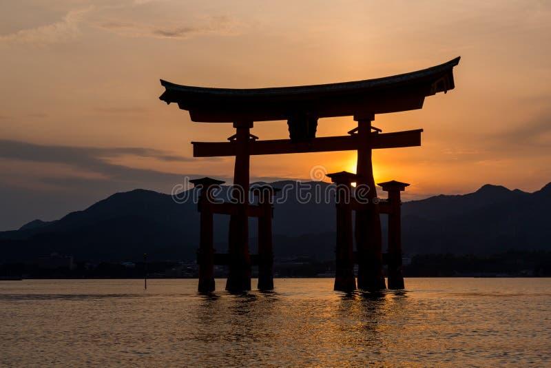 Miyajimaeiland - Silhouet van Itsukushima die Torii-Poort drijven bij zonsondergang royalty-vrije stock fotografie