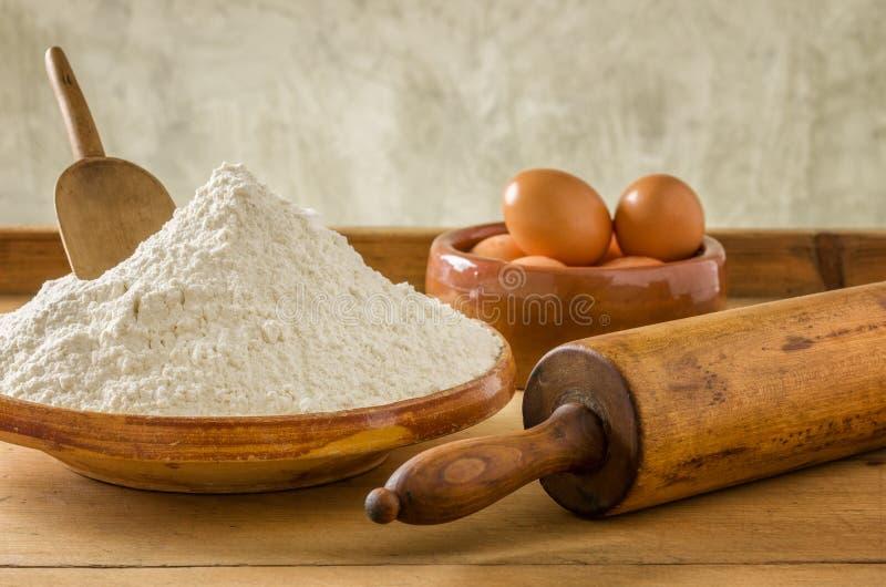 Mjöl, ägg och gammal kavel royaltyfria foton