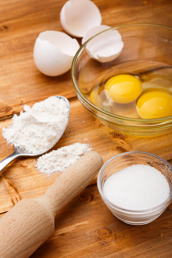 Mjöl ägg och saltar på trätabellen arkivbild