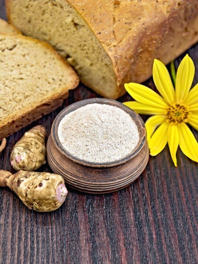 Mjöl av den Jerusalem kronärtskockan i lerabunke med bröd ombord fotografering för bildbyråer