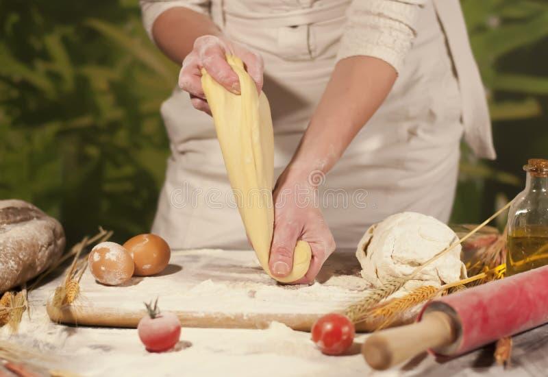 Mjöl för recept för kvinnabagarehänder som knådar pastasmör, tomatförberedelsedeg och gör bröd royaltyfri foto