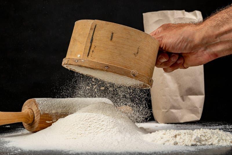 Mjöl som siktas till och med en gammal träsikt Tillbehör i hem- kök på en mörk tabell royaltyfri bild