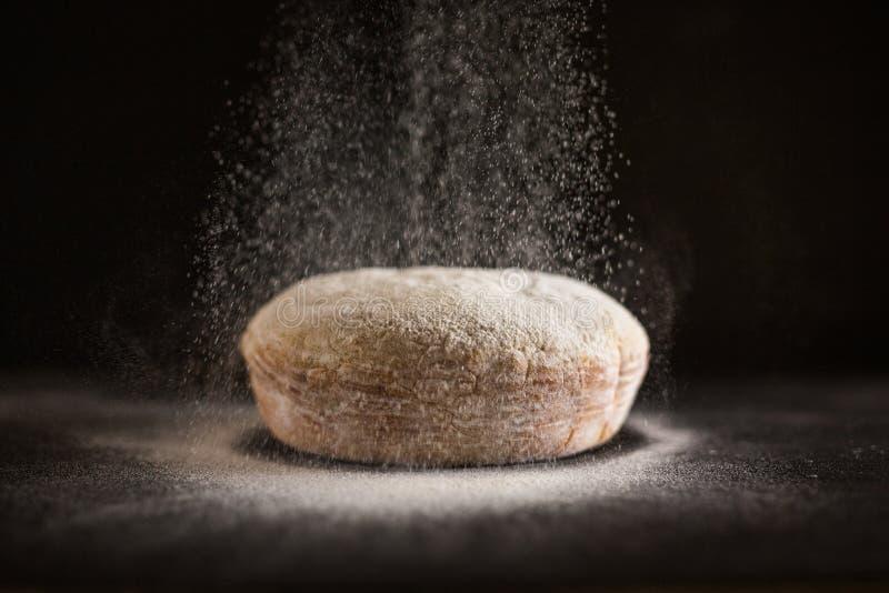 Mjöl som strilas på nytt bakat bröd arkivbild