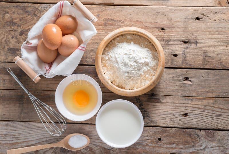 Mjölet i en träbunke, ägg, mjölkar och piskar för att slå fotografering för bildbyråer