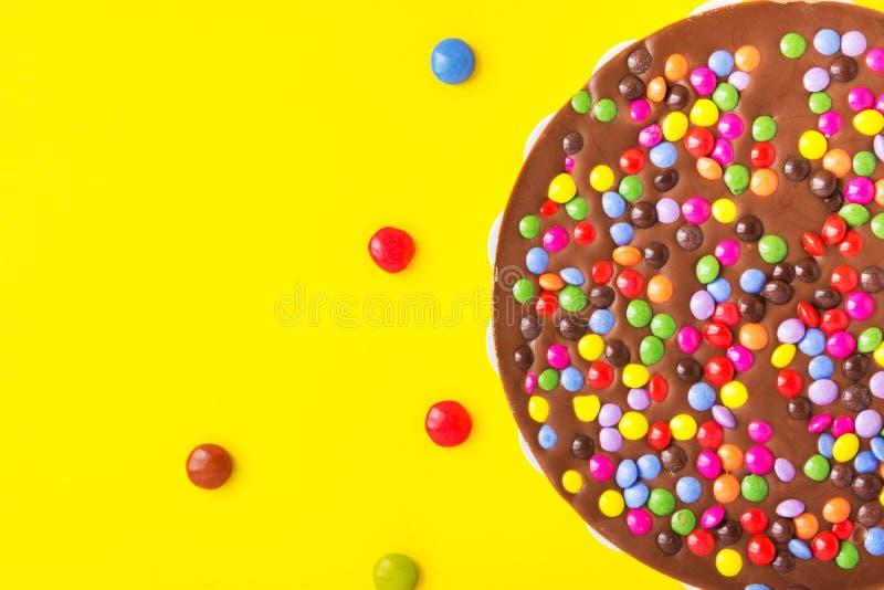 Mjölka chokladfödelsedagkakan med den mångfärgade glasade godisen strilar garnering på ljus gul bakgrund Ungeparti arkivfoton