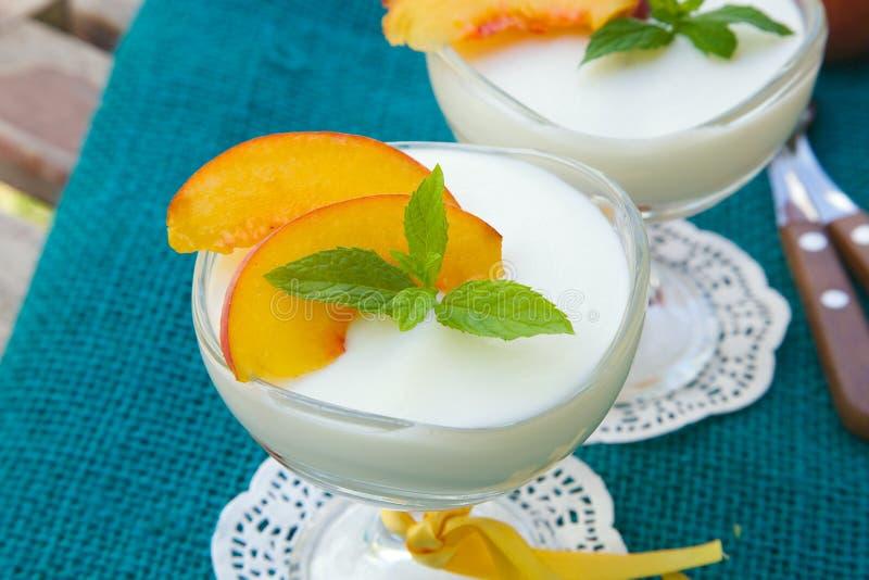 Mjölka efterrätten med persikor royaltyfri fotografi