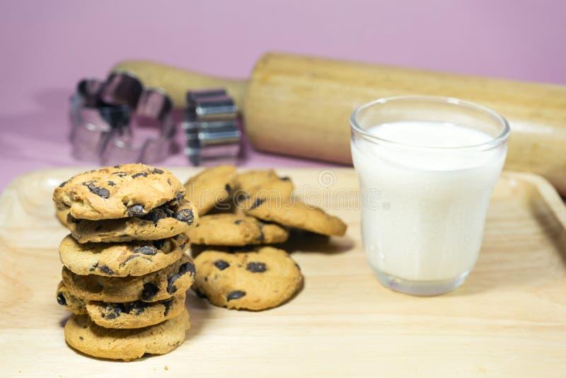 MJÖLKA EXPONERINGSGLAS, OCH exponeringsglas för SMÄLLARE A av mjölkar med högen av smällare på träöverkanttabellen royaltyfri foto