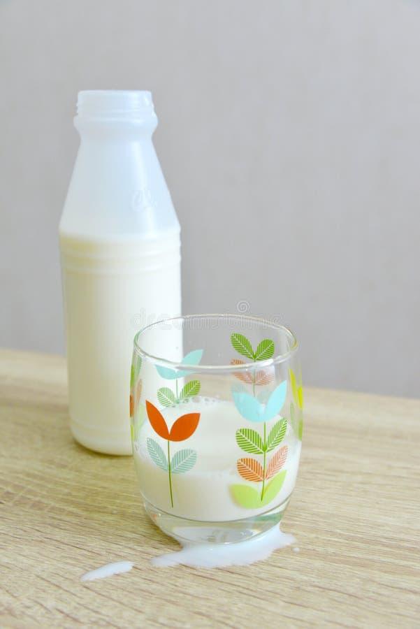Mjölka flaskan, ett partiskt fyllt glass, och spillt mjölka fotografering för bildbyråer