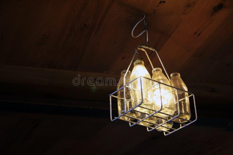Mjölka flaskbelysningljuskronan royaltyfria foton
