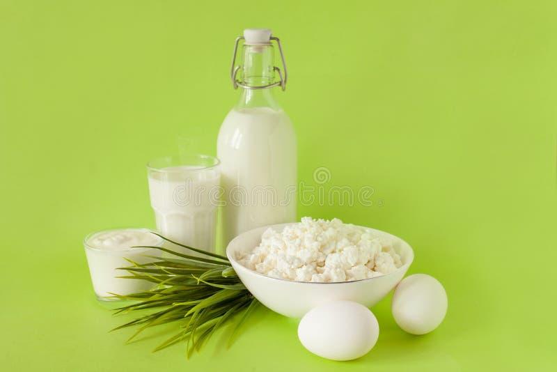 Mjölka i en keso för flaskägggräddfil, och ett exponeringsglas av mjölkar på en grön bakgrund med gräs i mitten av ramen royaltyfria foton