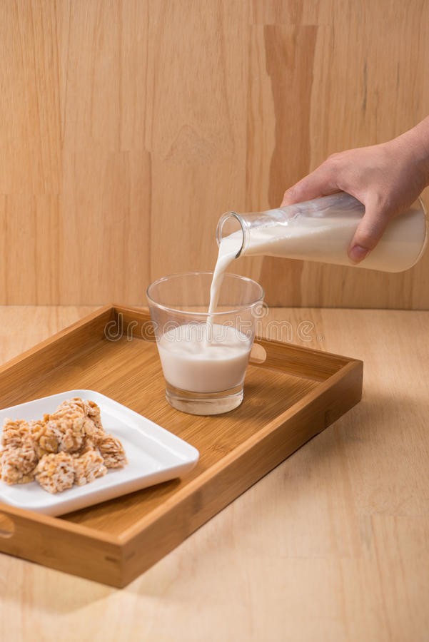 Mjölka med mandelgodisar på en trätabell royaltyfri fotografi