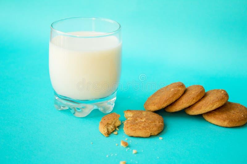 Mjölka och kexet på blå bakgrund fotografering för bildbyråer