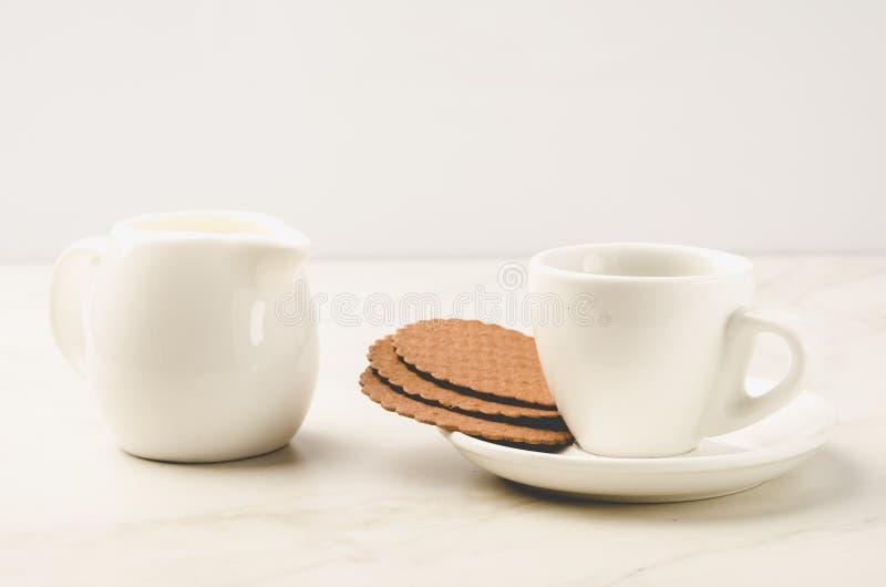 Mjölkar mjölkar den vita koppen för Coffe espresso med kakor och/den vita koppen för Coffe espresso med kakor och på en vit bakgr arkivfoton