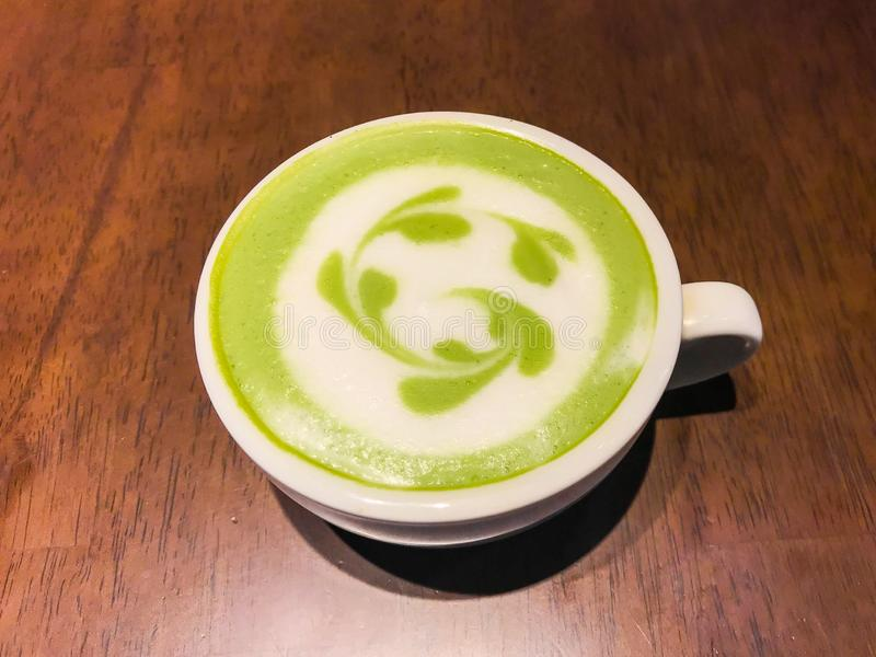 Mjölkar grönt te för den varma matchaen latte med krämigt mjölkar är blomma- eller växtmodellen, lite socker och tesked i en kopp royaltyfri bild