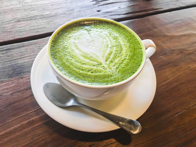 Mjölkar grönt te för den varma matchaen latte med krämigt mjölkar är denformade modellen, lite socker och tesked i en kopp på trä royaltyfri foto
