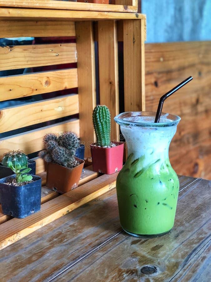 Mjölkar grönt te för is i exponeringsglas som överträffas med, fradga på trätabellen royaltyfri bild