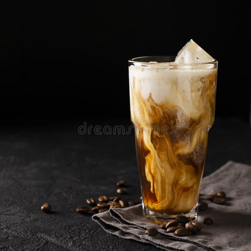 Mjölkar kallt brygdkaffe för högväxt exponeringsglas med is och på svart eller mörkt b arkivfoto