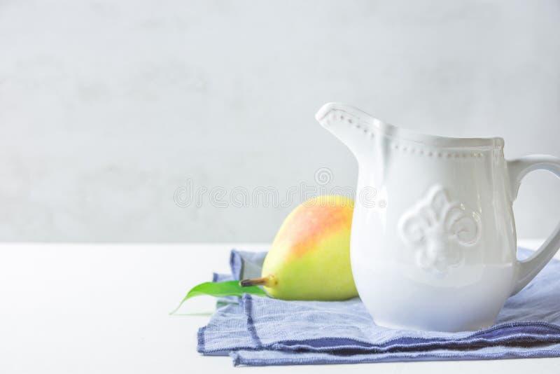 Mjölkar keramisk kräm för vit tappning tillbringareanseende på det vikta blåa mogna gula röda päronet för bomullslinneservetten p arkivbilder