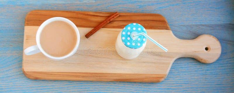 Mjölkar rånar tillbringaren för den kanelbruna pinnen för det blåa locket av därefter a och av kaffe royaltyfri foto