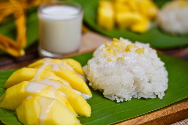 Mjölkar söta klibbiga ris för efterrätt med mangokokosnöten på bananträd arkivfoton