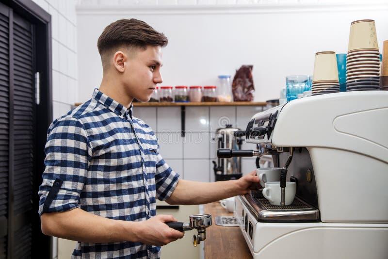 Mjölkar varm ånga för unga stiliga för baristahipsterdanande för kaffe för kafét för mannen korn för maskinen cappuccino för latt royaltyfria bilder