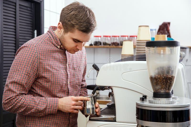 Mjölkar varm ånga för unga stiliga för baristahipsterdanande för kaffe för kafét för mannen korn för maskinen cappuccino för latt royaltyfri fotografi