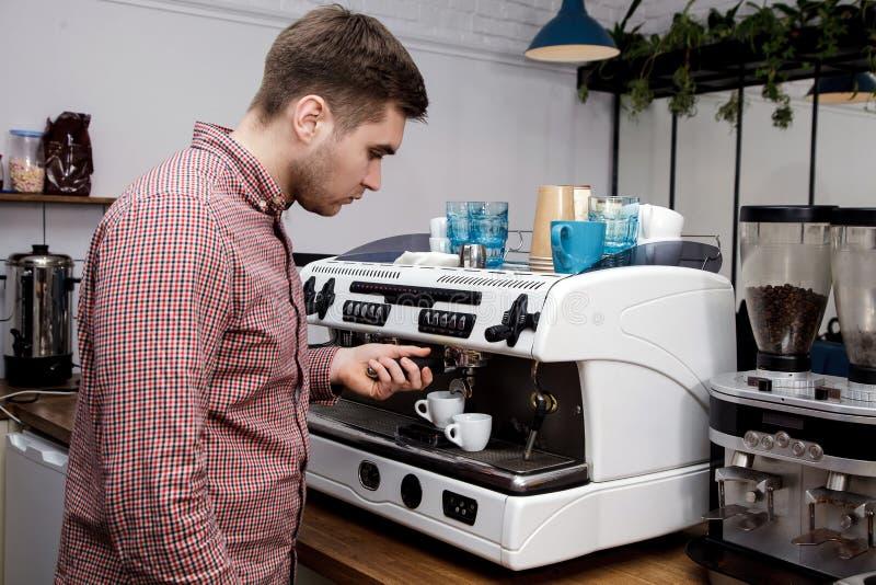 Mjölkar varm ånga för unga stiliga för baristahipsterdanande för kaffe för kafét för mannen korn för maskinen cappuccino för latt arkivfoto