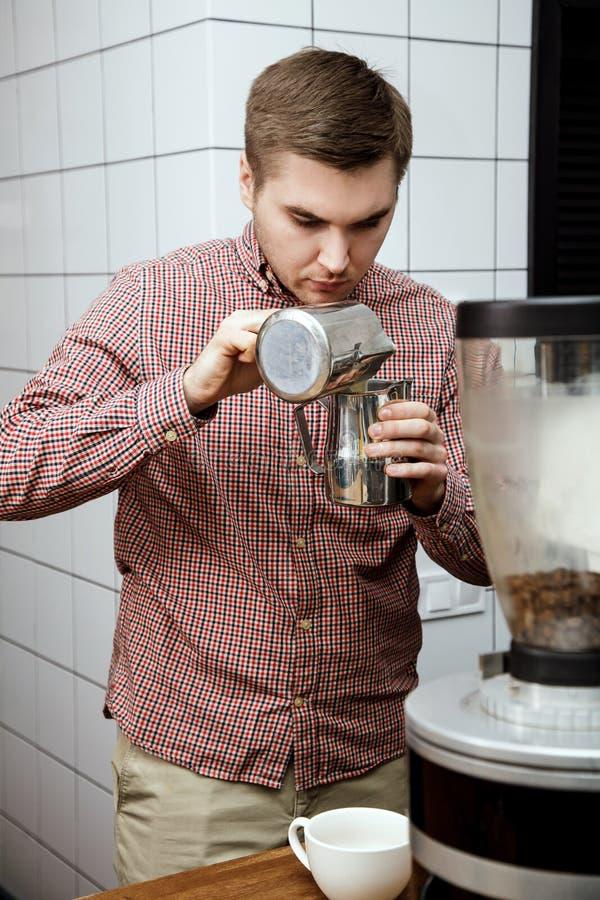 Mjölkar varm ånga för unga stiliga för baristahipsterdanande för kaffe för kafét för mannen korn för maskinen cappuccino för latt royaltyfri bild
