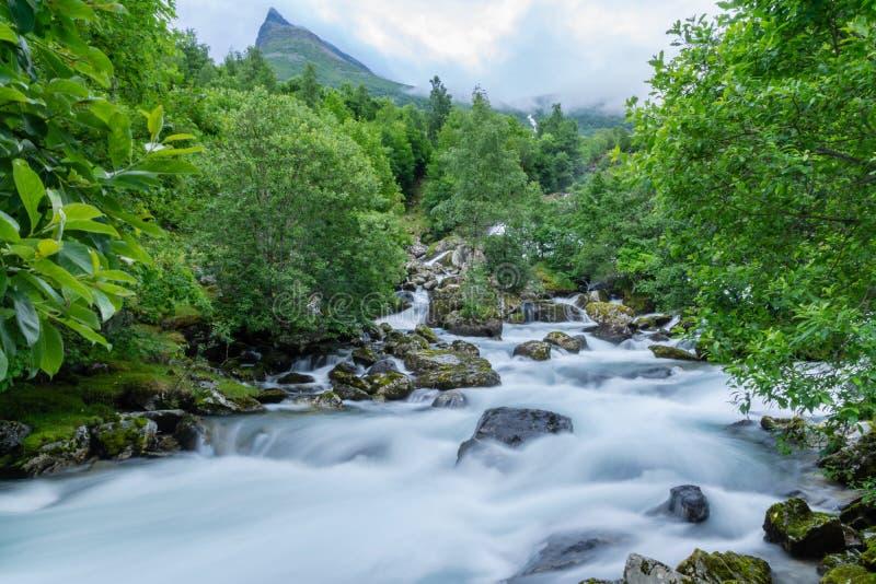 Mjuk disig vattenfall som kör ner en bergssida i Norge royaltyfri foto