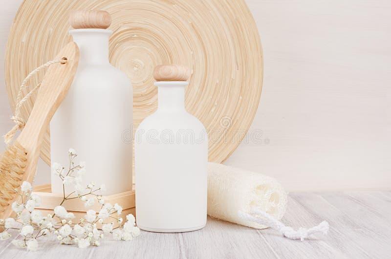 Mjuk elegant badrumdekor av vita skönhetsmedelflaskor med hårkammen, blommor på det vita wood brädet, åtlöje upp, kopieringsutrym royaltyfri foto