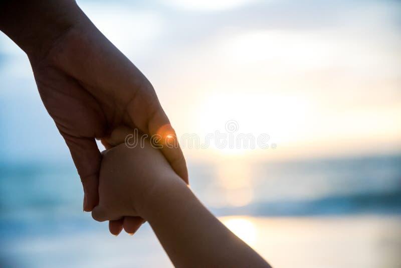 Mjuk fokusförälderhåll handen för litet barn under solnedgång arkivbilder