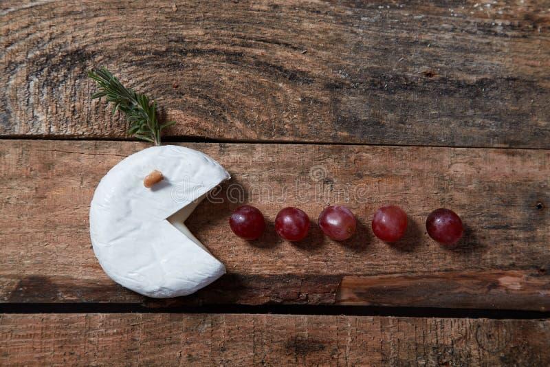 Mjuk gourmet- ost med druvor och rosmarin på trätabellen royaltyfria bilder