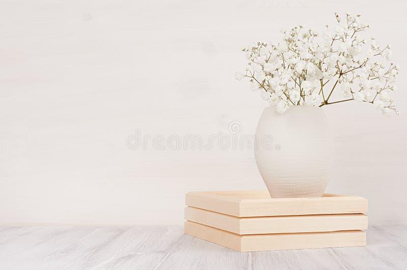 Mjuk hem- dekor av vita små blommor i keramisk vas på vit wood bakgrund royaltyfri bild