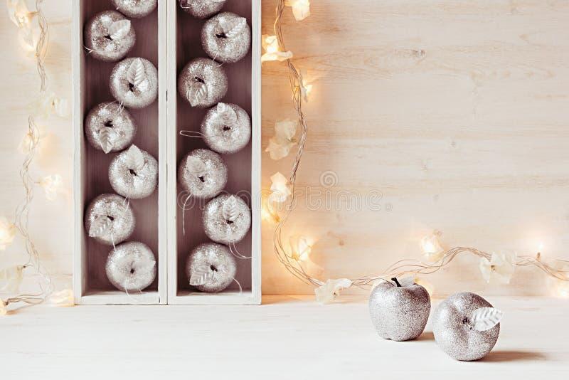 Mjuk hem- dekor för jul av silveräpplen och ljus som bränner i askar på en trävit bakgrund royaltyfria bilder