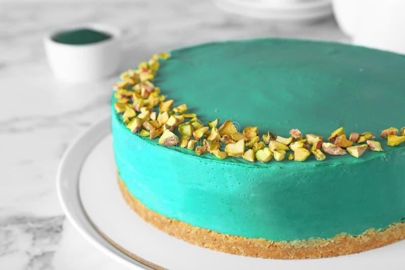 Mjuk homemade spirulina cheesecake med pistaschmandlar på marmor arkivbilder