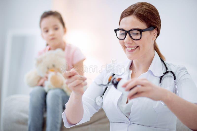 Mjuk kvinnlig doktor som behandlar flickan royaltyfri foto