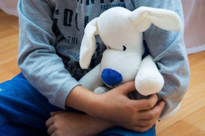 Mjuk leksak i händer för barn` s arkivbild