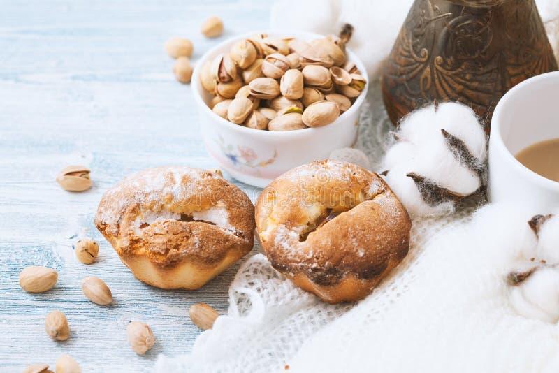 Mjuk muffin på en vit träbakgrund, med pistascher arkivfoton