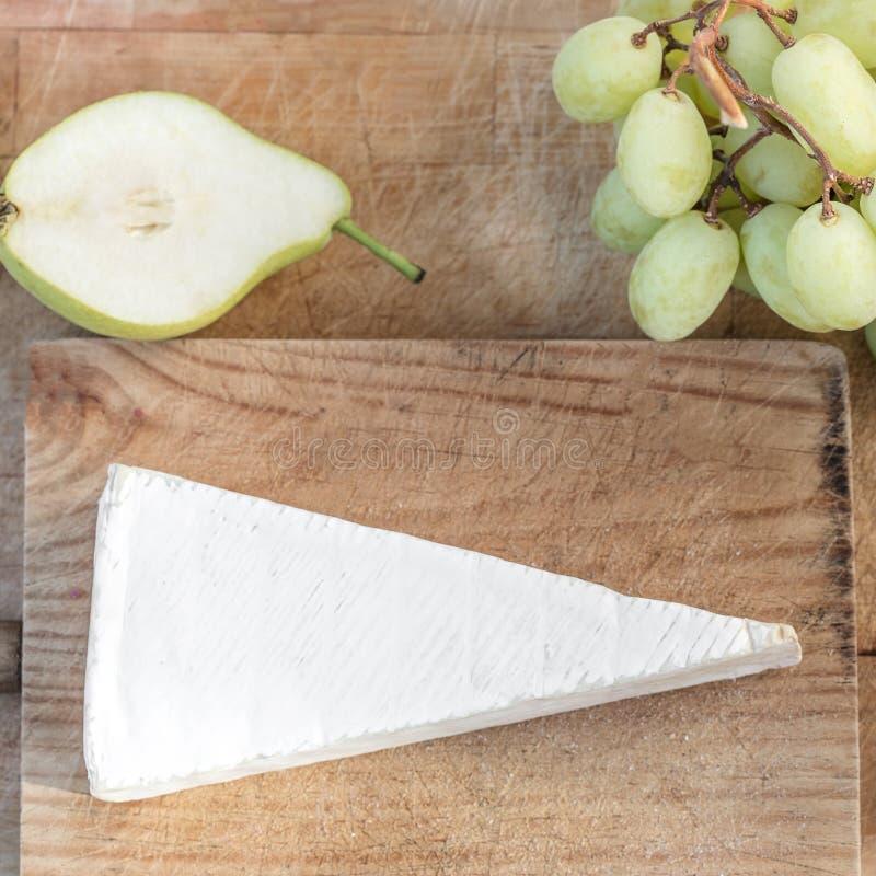 Mjuk ost på lantligt träbräde med päronet och druvor nytt arkivfoto