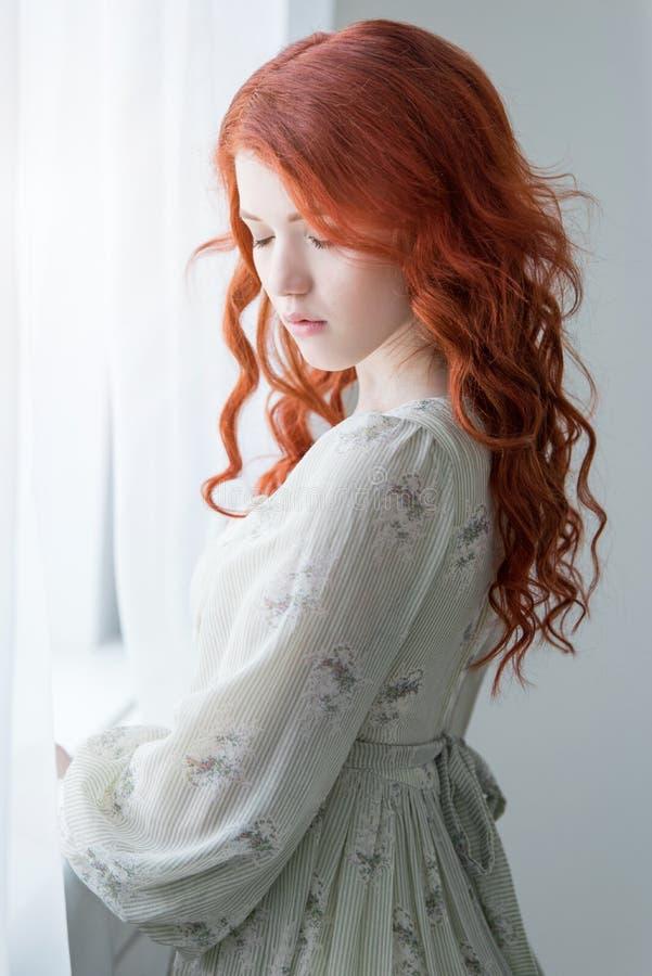 Mjuk retro stående av en ung härlig drömlik rödhårig mankvinna royaltyfria bilder
