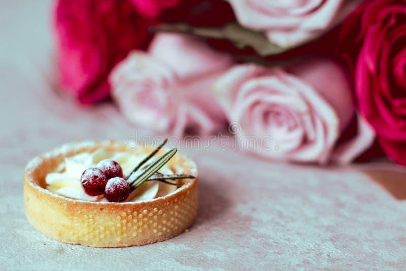 Mjuk romantisk gåva: söta kakor med kräm och bär och en bukett av rosa rosor på en ljus bakgrund arkivbilder