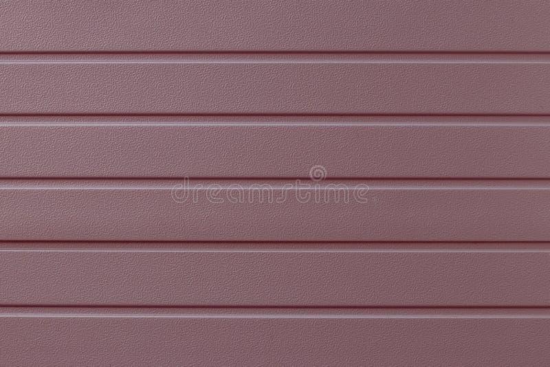 Mjuk rosa gjord randig stålyttersida Remsamodell på metalldörren Reflekterande metallisk cladding av väggen, textur Ribbad ros-fä fotografering för bildbyråer
