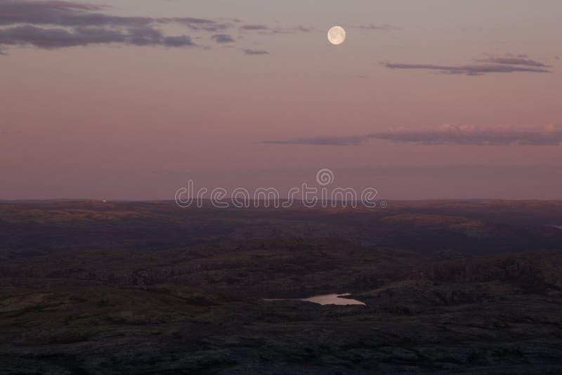 Mjuk rosa solnedgånghimmel över bergdalen med fullmånen royaltyfria foton