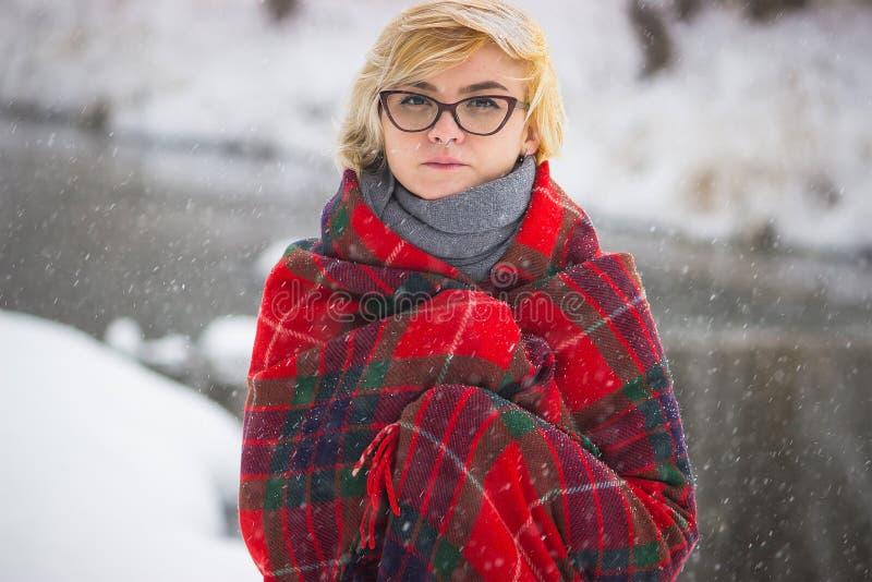 Mjuk stående av udda ensamt flickasammanträde i person för snöig skog för vinter utan vänner kvinnlig med ledset emotionellt arkivbild