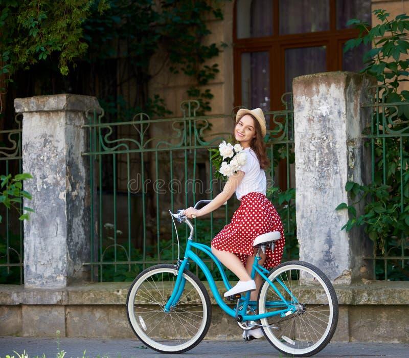 Mjuk ung kvinna på den blåa retro cykeln med pioner royaltyfria bilder