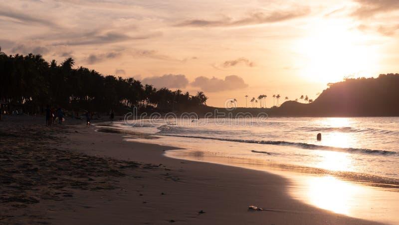 Mjuk vågtvätt över en lokal havsstrand vid solnedgången Tillfrisknande, lugna vågor av havet på sandstranden vid solnedgången Sun fotografering för bildbyråer