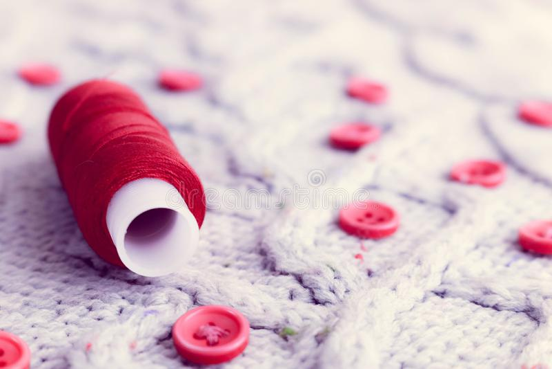 Mjuk varm naturlig tröja, tyger med en stucken modell av garn och röda små runda knappar för att sy och en skein av den röda tråd arkivfoto